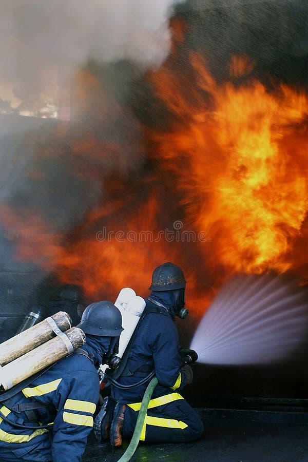 De mensen van de brand in actie het branden de bouw stock foto