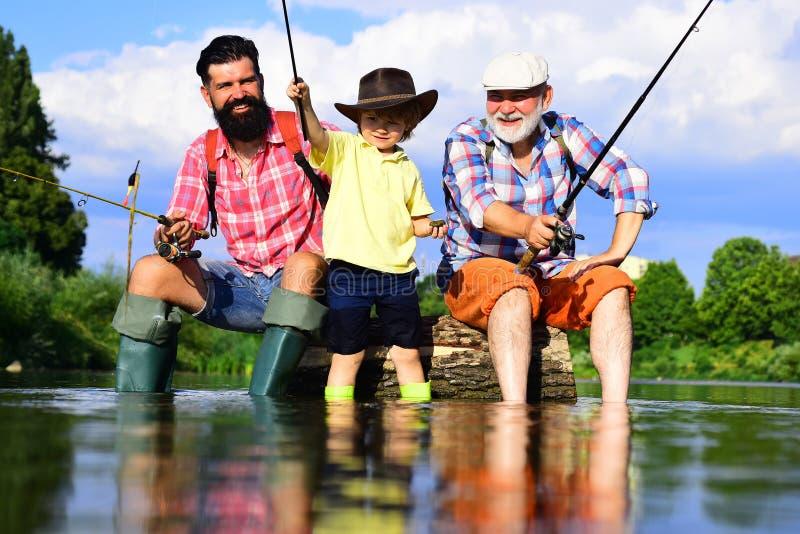 De mensen van generaties Mens met zijn zoon en vader die op rivier met hengels vissen De opa en de kleinzoon zijn vlieg vissend royalty-vrije stock afbeelding