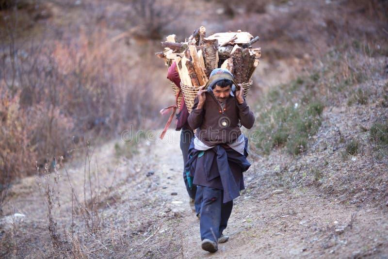De mensen van Gorkhas dragen zware mand in het Himalayagebergte stock foto's