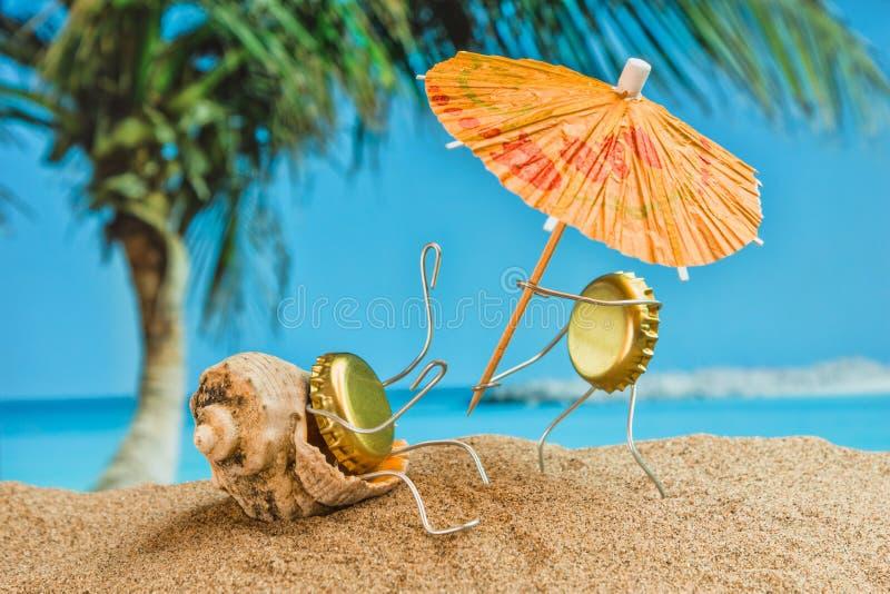 De mensen van het stuk speelgoed van bierkappen die op een zandig strand rusten stock foto's