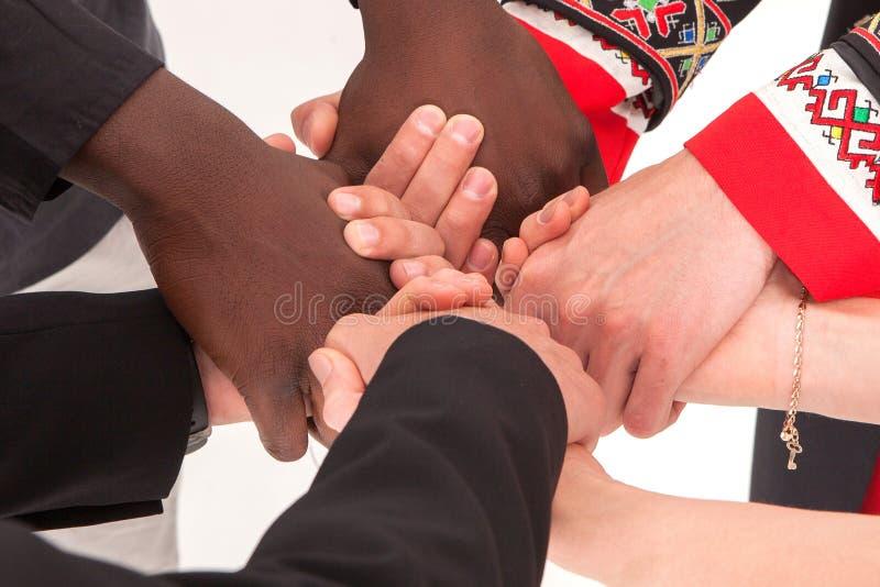 De mensen van verschillende nationaliteiten en godsdiensten houden handen royalty-vrije stock afbeelding