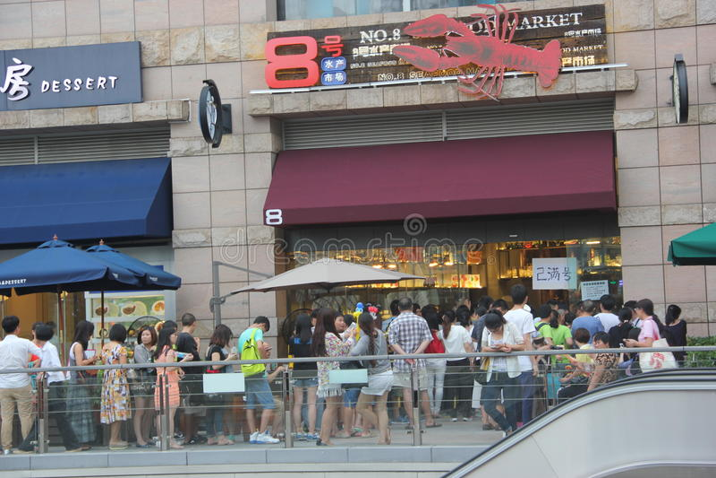 De mensen vormden omhoog voor diner in SHENZHEN een rij stock foto's