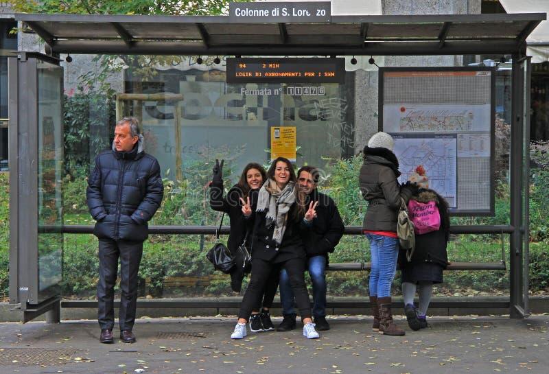 De mensen wachten binnen op bus op eindepost stock afbeeldingen
