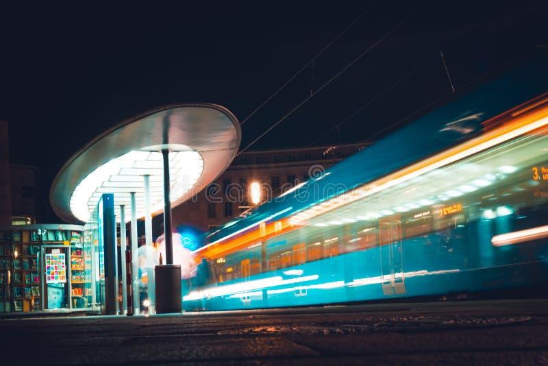 De mensen wachten op een stadstram bij nacht Duitsland, Kassel stock foto