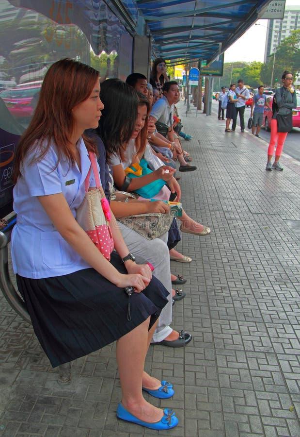 De mensen wachten op vervoer bij bushalte stock afbeelding