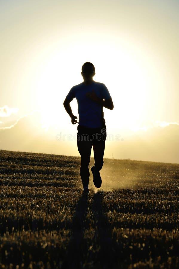 De mensen wegvloeiende weg van de silhouet jonge sport op het gebied van het plattelandsstro backlight bij de zomerzonsondergang stock foto