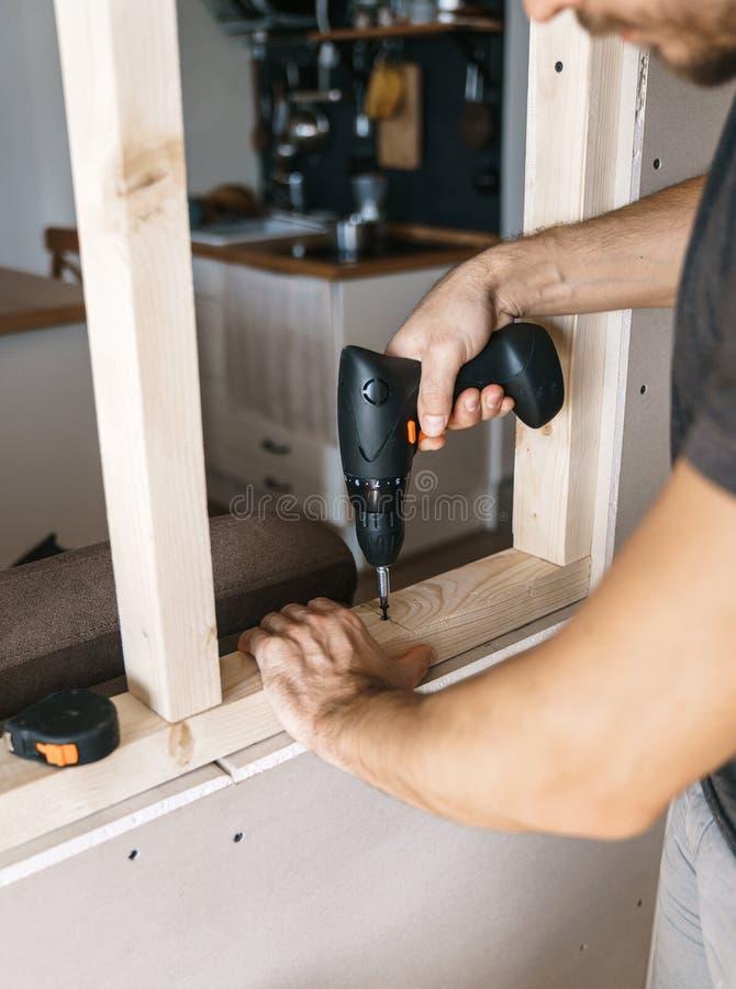 De mensen werken met een schroevedraaier, bevestigend een houten kader voor een venster in hun huis stock afbeeldingen