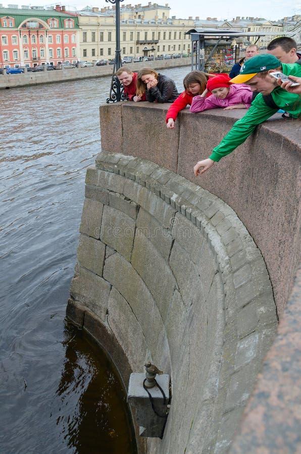 De mensen werpen muntstukken op voetstuk van chizhik-Pyzhik monument, St. Petersburg, Rusland stock afbeelding