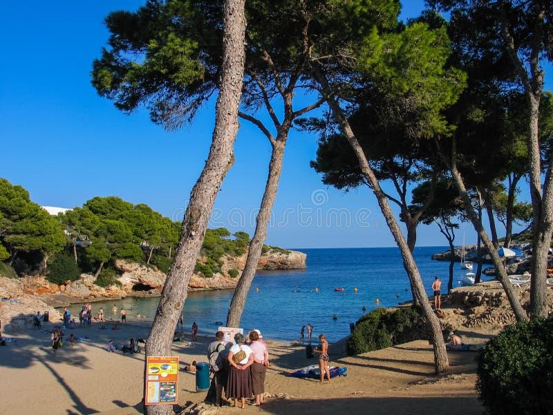 De mensen wonen strand op Cala Esmeralda baai in Majorca bij stock afbeeldingen