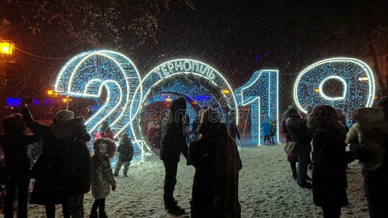 De mensen worden gefotografeerd dichtbij de grote lichte slingers De zware sneeuw viel royalty-vrije stock foto's