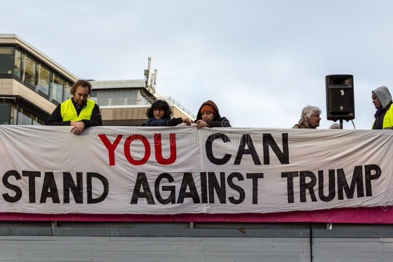De mensen zetten antidonald trump-banner op stock foto's