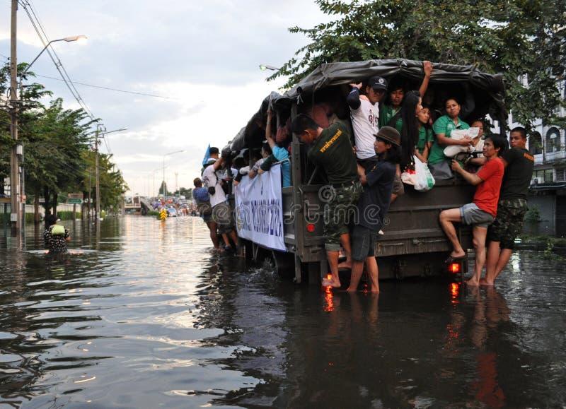 De mensen zetten in een legervrachtwagen om in een overstroomde straat in Bangkok, Thailand, in Oktober 2011 stock afbeeldingen