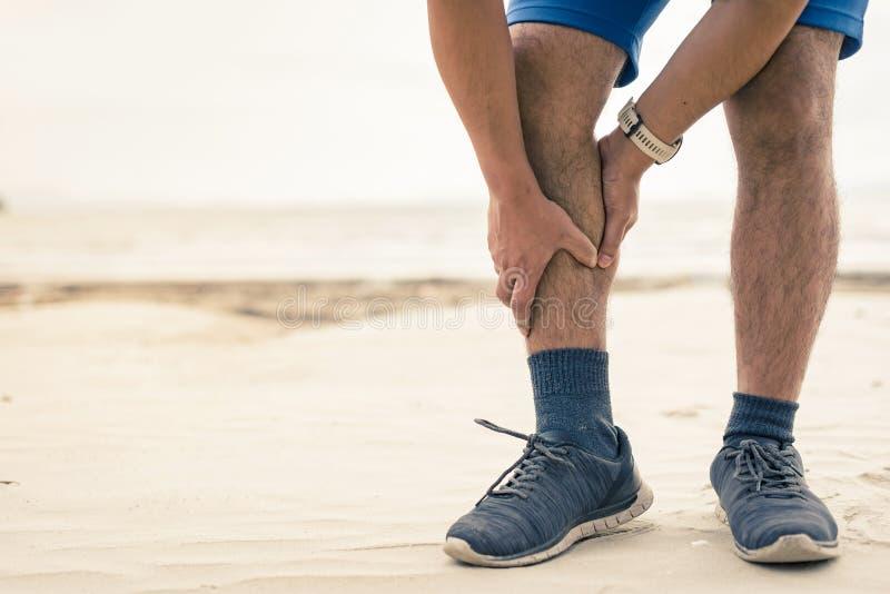 De mensenagent houdt zijn sporten verwond been op de strandachtergrond stock afbeeldingen