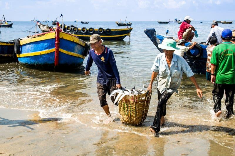 De mensenarbeiders die diepe bamboemand dragen laadden met vissen bij Lange Hai-vissenmarkt, de provincie van Bedelaarsria vung t stock afbeelding