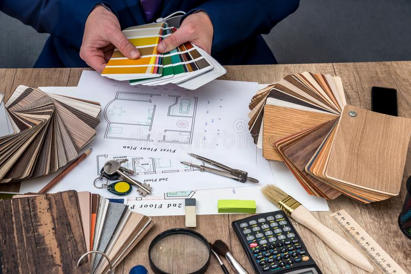 De mensenarchitect trekt een huisplan met kleurenpalet voor meubilair stock afbeeldingen