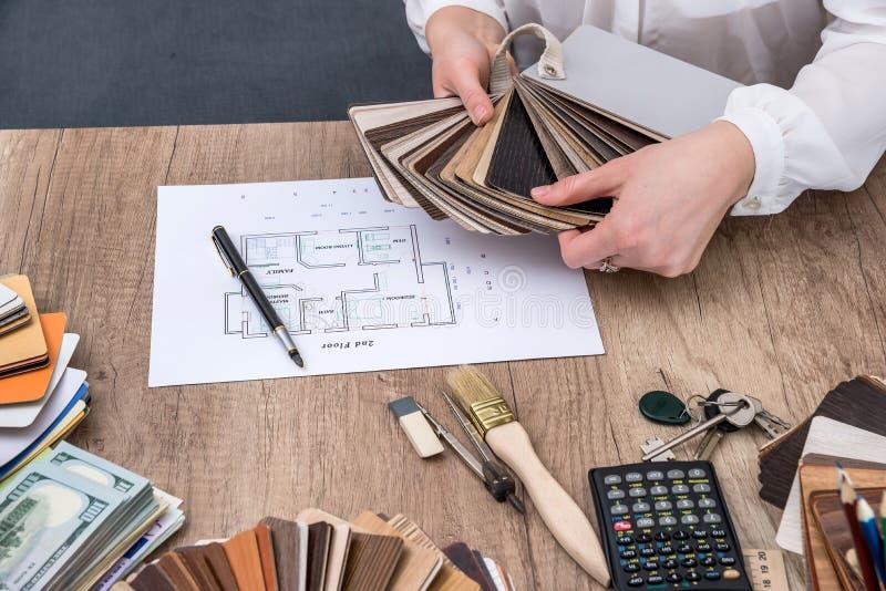 De mensenarchitect trekt een huisplan met kleurenpalet voor meubilair, royalty-vrije stock afbeelding