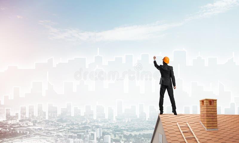 De mensenarchitect trekt silhouet van moderne stad op blauwe hemel Gemengde media stock afbeelding
