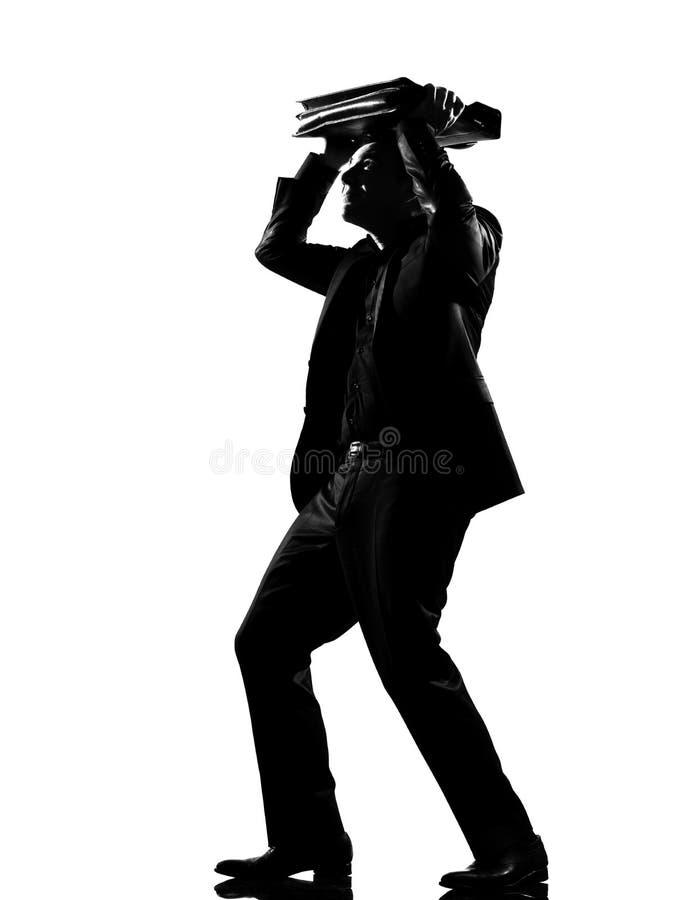 De mensenbeveiliging van het silhouet met zijn aktentas stock foto's