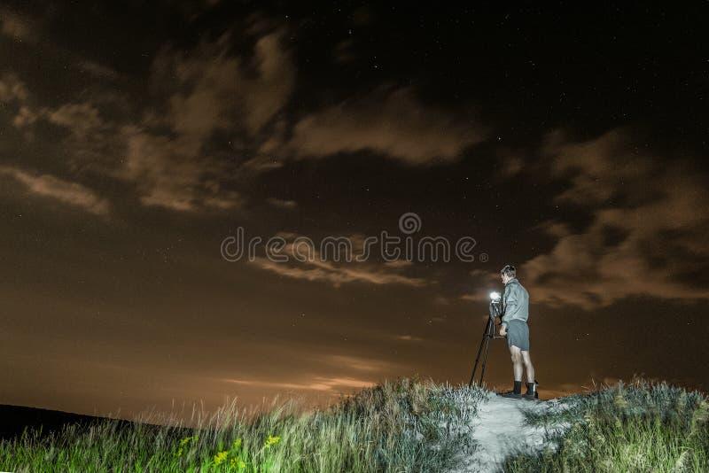 De mensenfotograaf neemt beelden van een nachtlandschap op een hoge heuvel stock foto