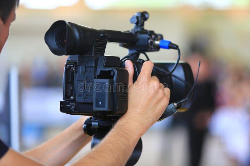 De mensenhand houdt digitale zwarte videocamera royalty-vrije stock afbeeldingen
