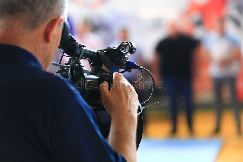 De mensenhand houdt digitale zwarte videocamera stock afbeelding