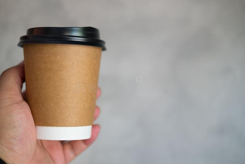 De mensenhand houdt een document kop van koffie stand om weg te halen royalty-vrije stock afbeelding