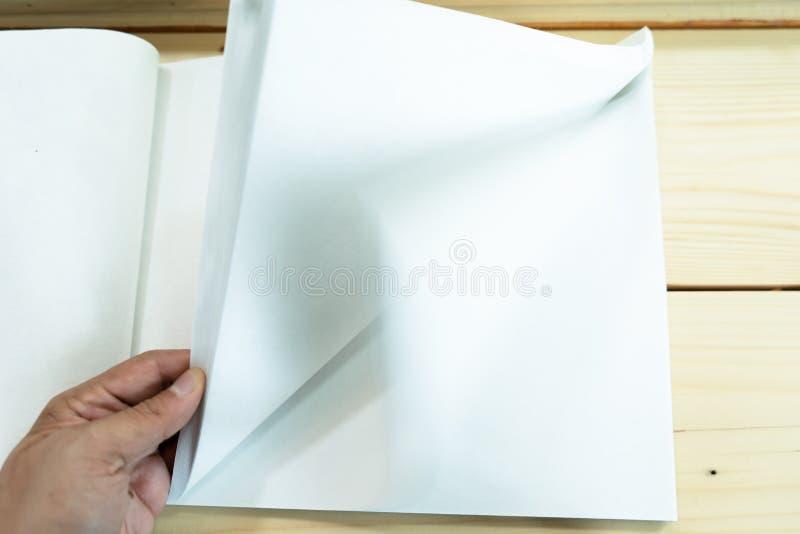 De mensenhand opent het witte lege notitieboekje op de houten lijst stock foto's