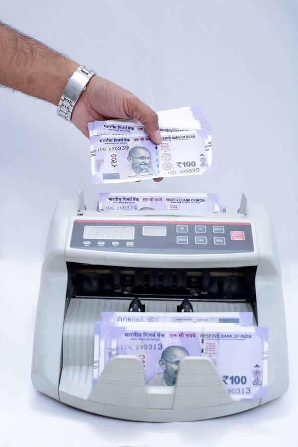 De mensenhand zet nieuwe 100 Roepiesnota's in contant geld tellende machine royalty-vrije stock foto's