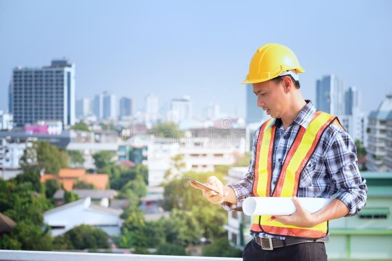 De menseningenieurs bevinden zich bij lange gebouwen en de bespreking over celtelefoons stock foto's