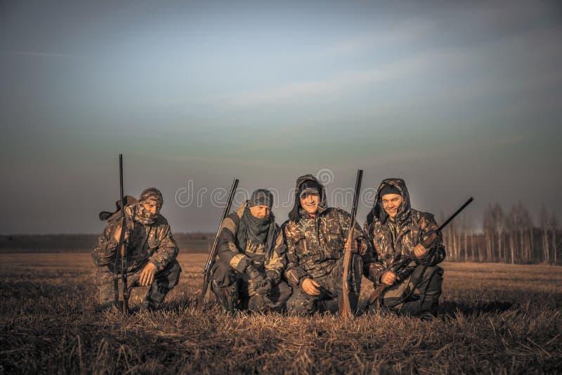 De mensenjagers groeperen teamportret in het landelijke gebied stellen samen tegen zonsopganghemel tijdens jachtseizoen Concept v royalty-vrije stock foto's