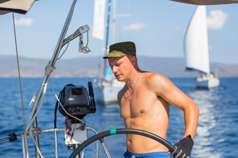 De mensenkapitein bij de roercontroles van een varend jacht tijdens overzeese boten rent Sport stock afbeelding