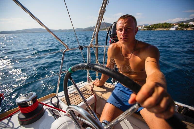 De mensenkapitein stelt een varend jacht op de open zee in werking Sport stock foto