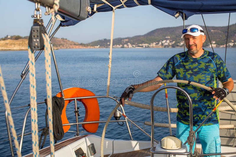 De mensenkapitein stuurt boot varend jacht op het Egeïsche Overzees Sport stock fotografie