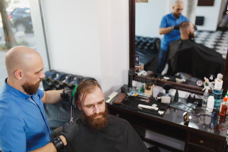 De mensenkapper dient de cliënt in de salon royalty-vrije stock foto