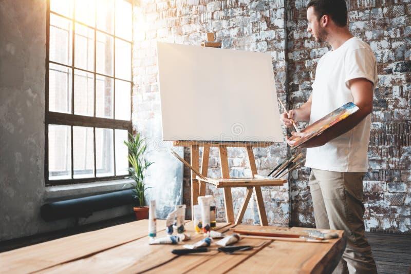 De mensenkunstenaar bevindt zich voor een leeg canvas op schildersezel met palet in de studio van de zolderkunst Het mannelijke p stock afbeelding