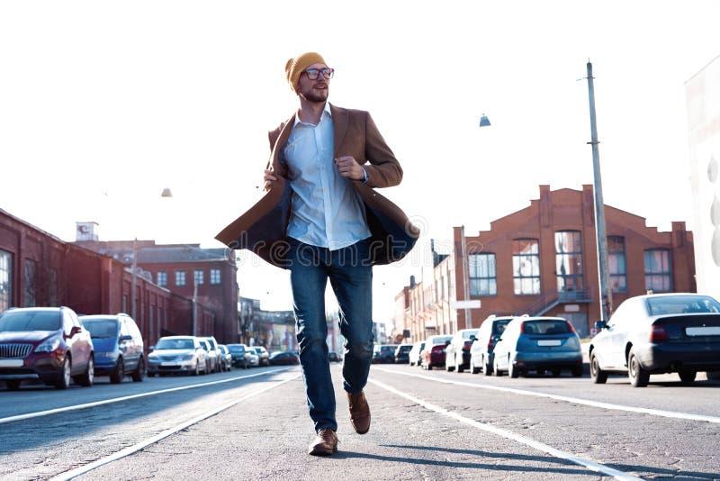 De mensenportret van de manier Jonge mens in glazen die laag dragen die onderaan de straat lopen stock afbeeldingen