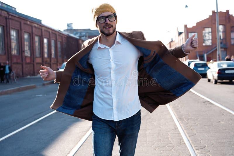 De mensenportret van de manier Jonge mens in glazen die laag dragen die onderaan de straat lopen royalty-vrije stock afbeelding