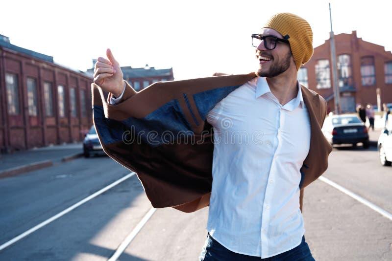 De mensenportret van de manier Jonge mens in glazen die laag dragen die onderaan de straat lopen stock foto
