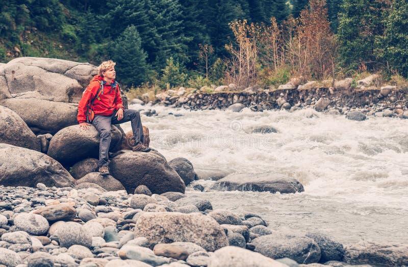 De mensenreiziger zit op de bank van de bergrivier royalty-vrije stock fotografie