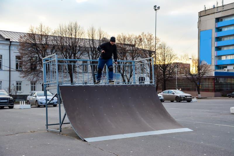 De mensenrol die van de vrije tijdsactiviteit in centraal van de stad op de zonsondergang schaatsen De winter stock afbeelding