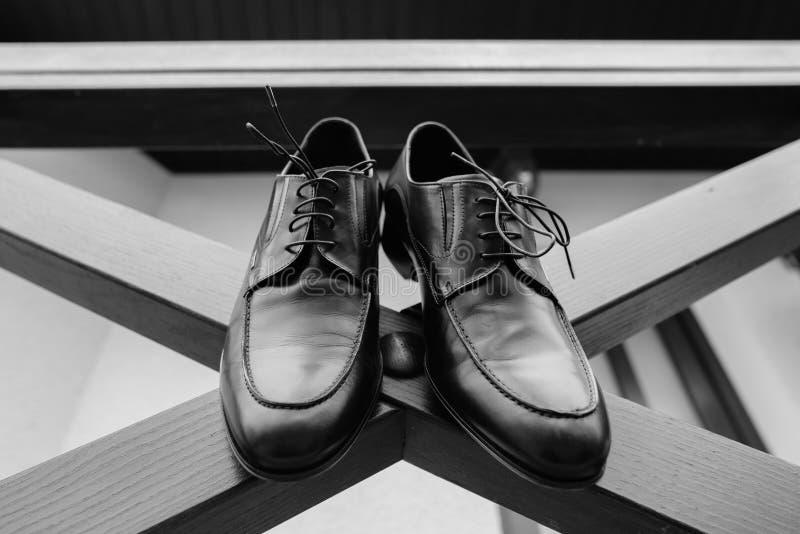 De mensenschoenen op vloer sluiten omhoog zwarte kleur Dure glanzende opgepoetste leer mannelijke schoenen die zich bij neutrale  stock foto