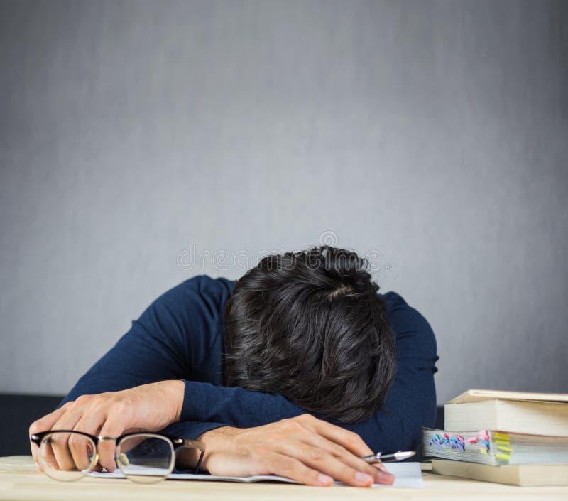 De mensenslaap op het werk houten bureau, bestudeert en vermoeide hard concept stock foto's