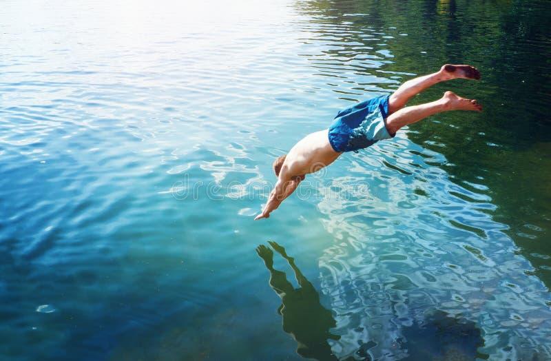 De mensensprongen zoals vissen in het water van het meer, zwemt, geniet van doorbrengend tijd aan de zomervakantie stock afbeeldingen