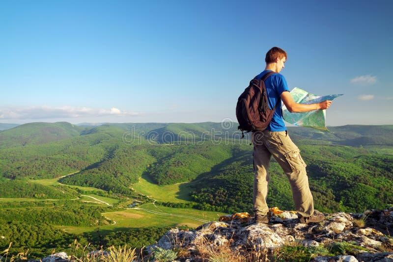 De mensentoerist in berg las de kaart. Mens bovenop berg. stock afbeeldingen