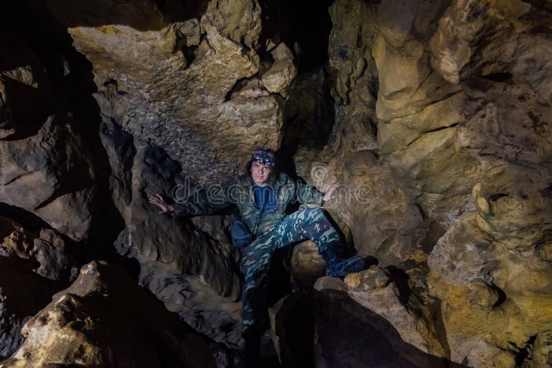 De mensentoerist in camouflagekostuum onderzoekt hol royalty-vrije stock afbeelding