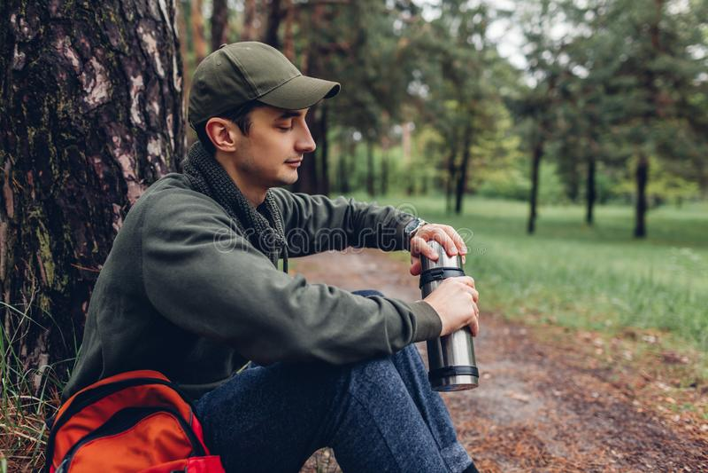 De mensentoerist opent thermosflessen met hete thee in de lente het bos Kamperen, het reizen en sportconcept stock foto