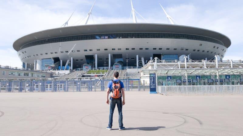 De de mensentoerist van de voetbalventilator met een rugzak bevindt zich en bekijkt de Gazprom-Arena in St. Petersburg Centraal s stock foto
