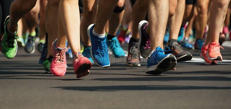 De mensenvoeten van het marathon lopende ras op stadsweg stock foto