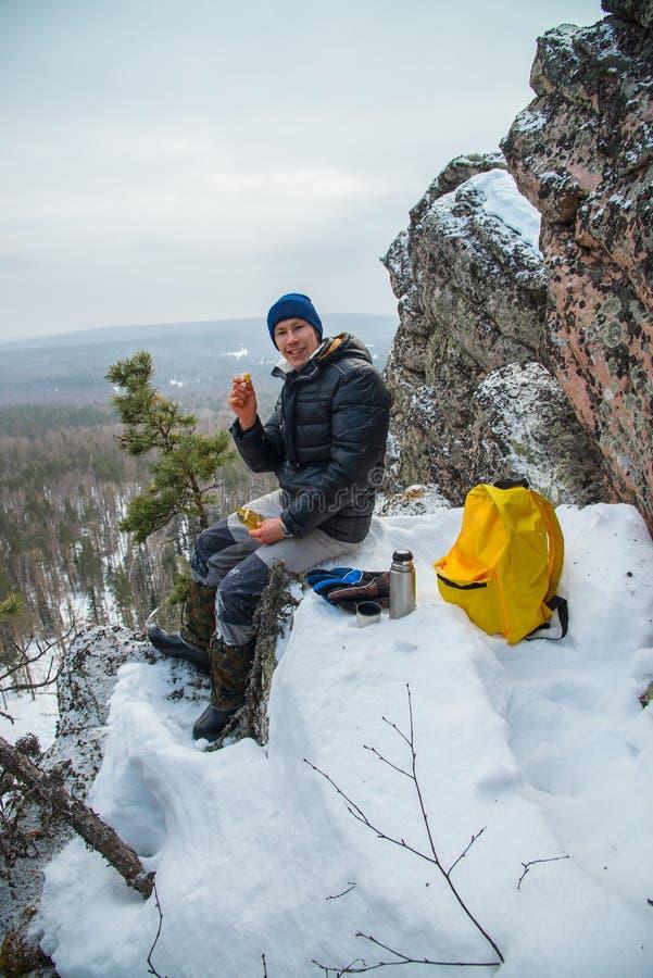 De mensenwandelaar heeft een rust bij bergbovenkant, het drinken thee en het eten tijdens de winteravontuur stock fotografie