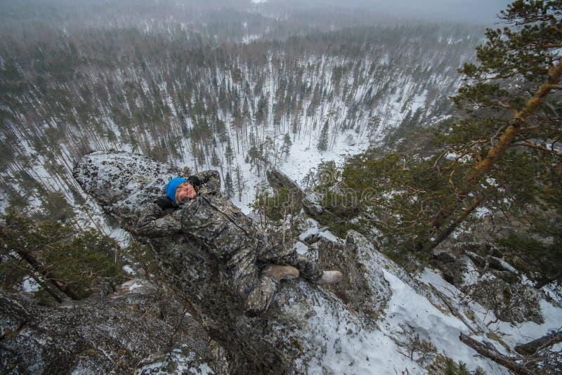 De mensenwandelaar heeft rust bij bergbovenkant, ontspant het liggen op rots stock foto's